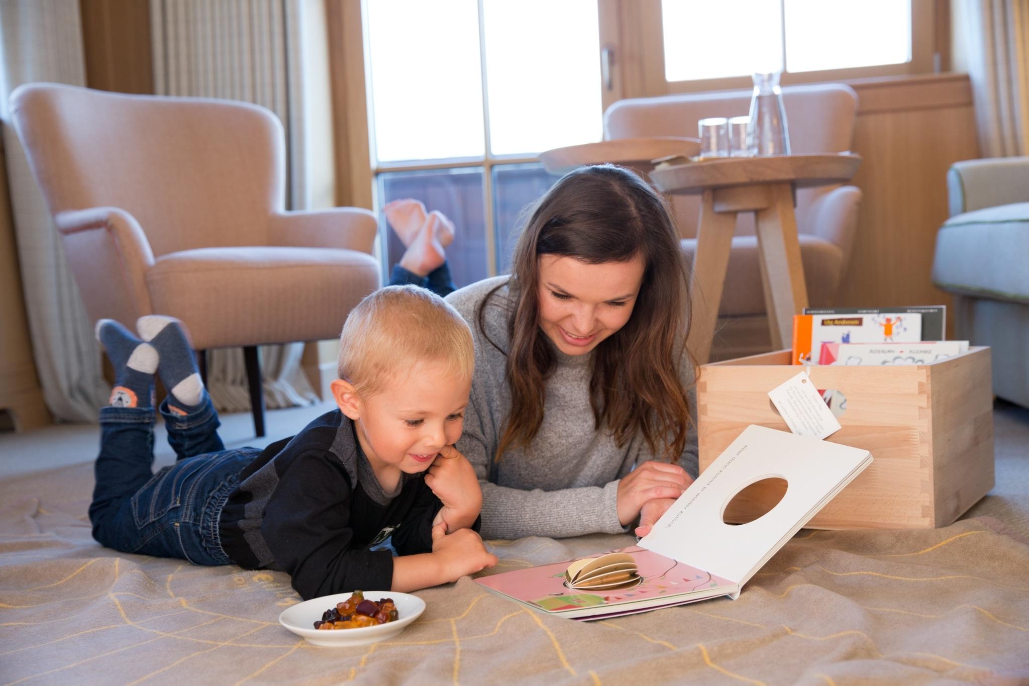 Frau und Kind lesen ein Buch aus der Bücherkiste, die auf jedem Zimmer im Literatur- und Kulturhotel Sonnenburg zu finden ist