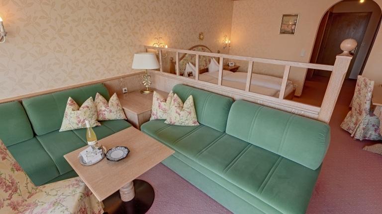 Blick über das Komfort Doppelzimmer in Lech am Arlberg im Landhaus Sonnenburg mit Doppelbett und Sitzmöbeln