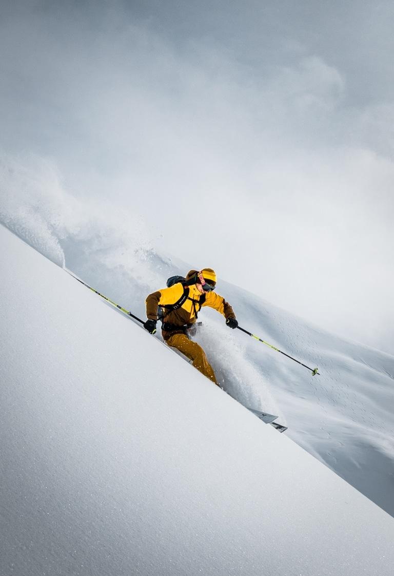 Symbolbild für Skiurlaub am Arlberg: Skifahrerin während einer Tiefschneeabfahrt in Lech