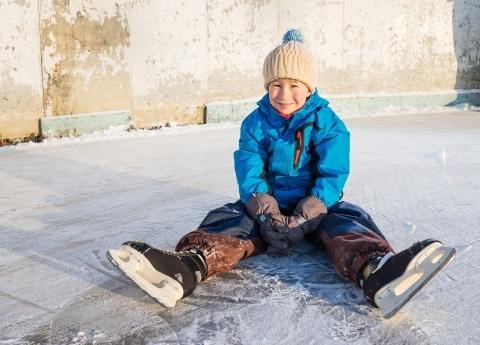 Symbolbild Eislaufen am Arlberg: kleiner Junge mit Schlittschuhen sitzt auf der Eislaufbahn in Zürs