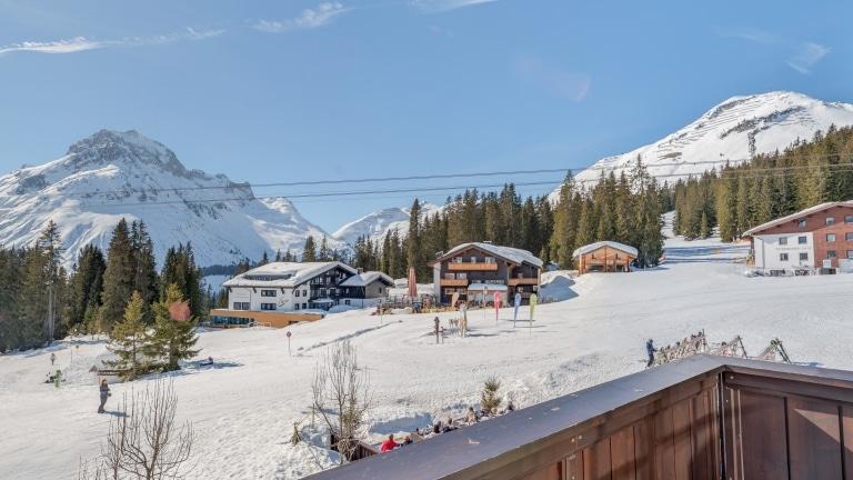 Symbolbild für Skihotel Arlberg: Ausblick vom Balkon der Gold Junior Suite des Luxushotel Sonnenburg auf verschneite Berge und die Skipiste