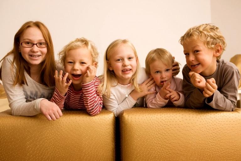 Symbolbild für Familien Hotel Kinderbetreuung: fünf lachende Kinder im Alter von 1 bis 12 Jahren knien auf einem Sofa im Österreichischen Oberlech am Arlberg