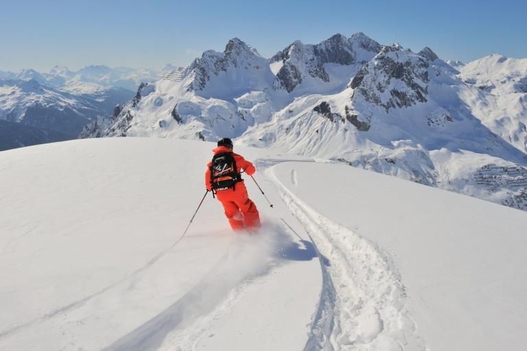 Symbolbild Freeriden Arlberg: Skifahrer fährt im Skiurlaub am Arlberg eine Tiefschneeabfahrt