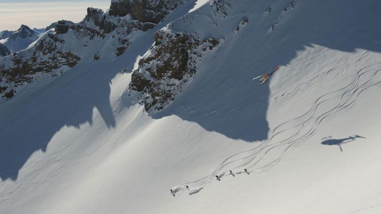 Symbolbild für Heliskiing Arlberg: Helikopter fliegt über Skifahrern in den Arlberger Alpen