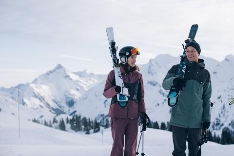 Symbolbild für Lech Hotels Ski in Ski out: Zwei Skifahrer tragen ihre Skiausrüstung