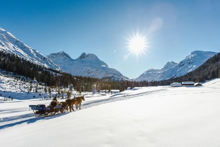Pferdeschlittenfahrt am Arlberg vor verschneiter Berglandschaft