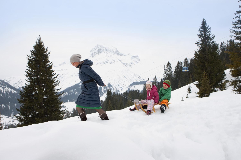 Symbolbild Rodeln in Österreich: eine Familie im Winterurlaub beim Rodeln in Österreich