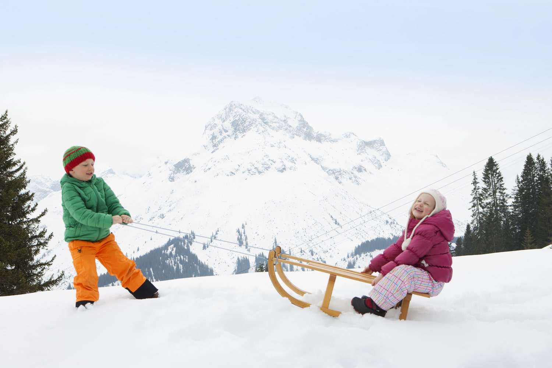 Kinder spielen im Familienurlaub vor dem Family Hotel Sonnenburg im Schnee