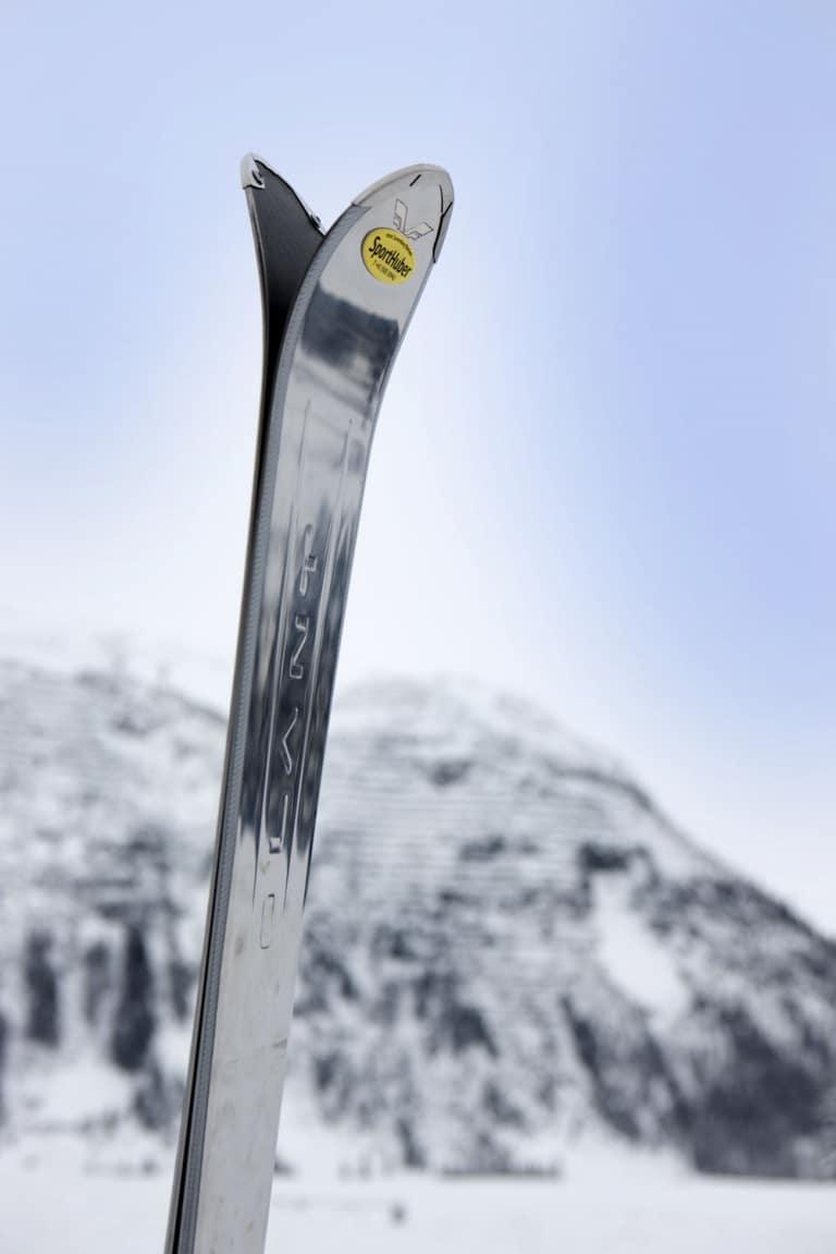 Symbolbild für Skiverleih Oberlech: Ski mit Logo des Skiverleih Sport Huber steck im Schnee