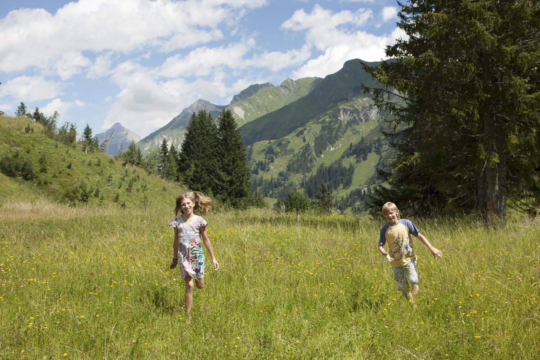 Kinder lieben es, beim Familienurlaub in den Berge im Sommer auf Bergwiesen zu spielen