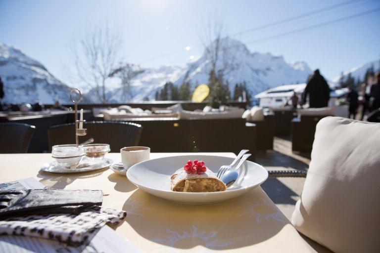 Zu Mittag speisen Sie auf der Sonnenterrasse der Sonnenburg typisch alpin, am Nachmittag servieren wir Ihnen hausgemachte Mehlspeisen mit einzigartiger Aussicht auf die majestätischen Gipfel des Arlbergmassivs.